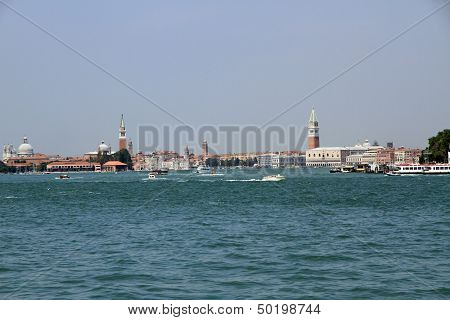 Skyline Of Venice With Steeples, Boat And Ferry In The Adriatic Sea