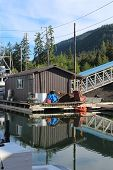 A float house in Shoemaker Bay harbor at Wrangell, Alaska on a calm sunny summer day. poster