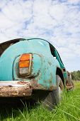Old abandoned car and blue cloudy sky poster