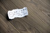 Motivational messagewritten on piece of paper on a wood background. Space for uour text. poster
