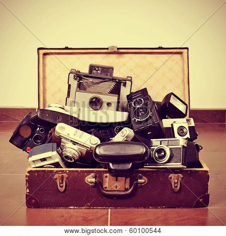 picture of a pile of old cameras in an old suitcase, with a retro effect