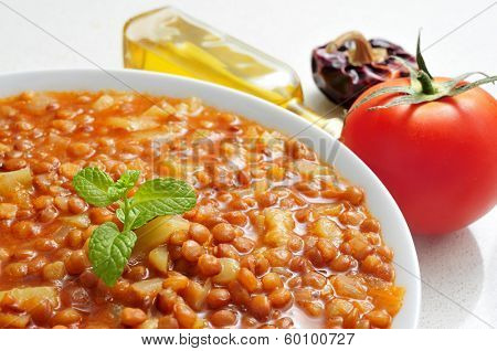 closeup of a bowl with lentil stew and olive oil and some vegetables in the background