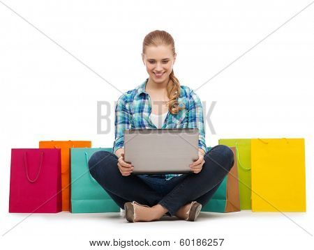 shopping, technology and internet concept - smiling girl with laptop computer and shopping bags over white background