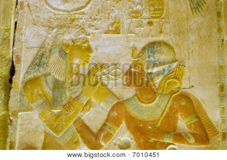 An ancient egyptian hieroglyphic carving showing the goddess Hathor, with her cow horn crown, placing the sacred ankh cross in front of the Pharoah Seti I.  Painted carving on a wall of the Temple of Osiris at Abydos, Egypt. poster