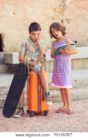 Young couple with suitcase in exterior. Romantic scene poster