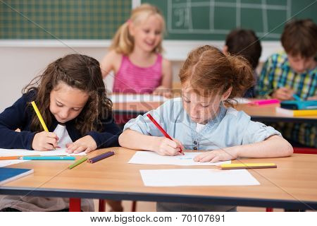 Two Young Girls Working Hard In Class
