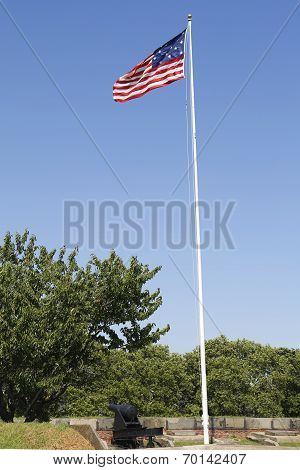 Old cannon and 15-star 15-stripe Star Spangled Banner American flag at Fort Jay on Governors Island