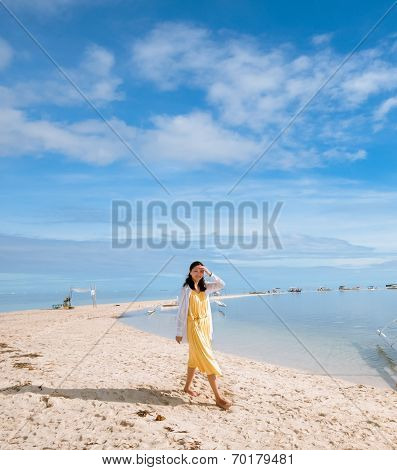 young girl walks on long narrow beach, smiling