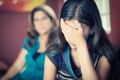 Teenager problems - Teenage girl cries while her mother looks at her on the background poster