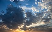 Cloudscape with the sun rays radiating from behind the cloud poster