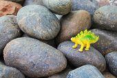 Plastic dinosaur toy on pebble stone background poster