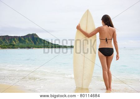 Surfer woman going surfing standing with surfboard on Waikiki Beach, Oahu, Hawaii. Female bikini girl walking with surfboard living healthy active lifestyle on Hawaiian beach. Asian Caucasian model.