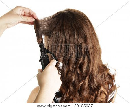 Stylist using curling iron for hair curls, close-up, isolated on white poster