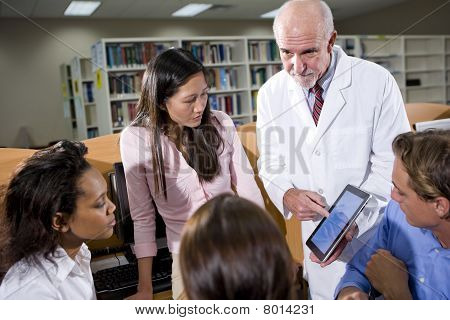 College Students With Teacher Talking In Library