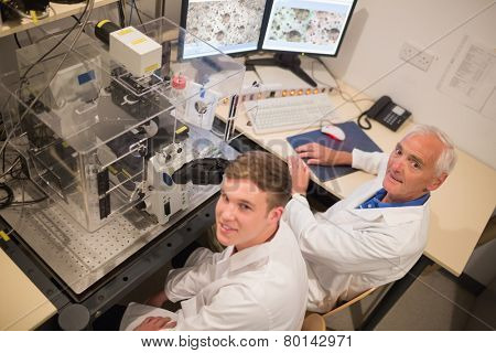 Biochemist and student looking at microscopic images on computer at the university