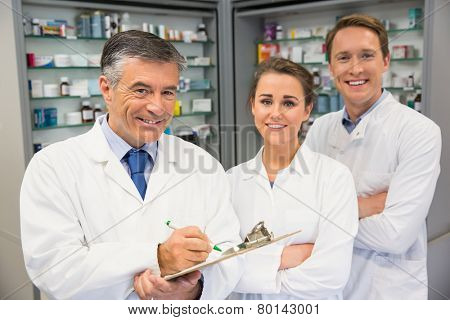 Team of pharmacists smiling at camera at the hospital pharmacy