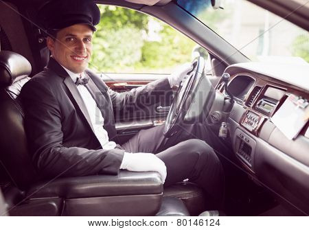 Limousine driver smiling at camera in his limo