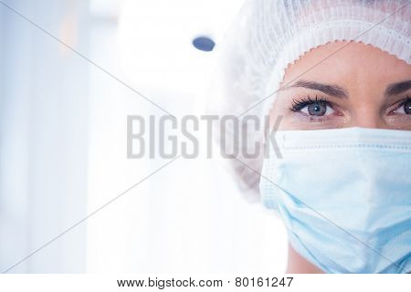 Dentist in surgical mask and cap looking at camera at the dental clinic