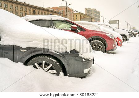 Snow covered cars in the street