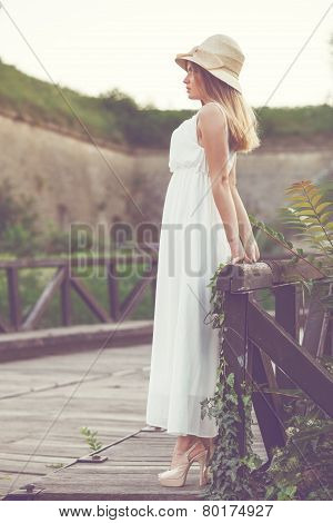 Beautiful Young Woman In An Elegant White Dress With A Hat On His Head, Standing On A Wooden Bridge