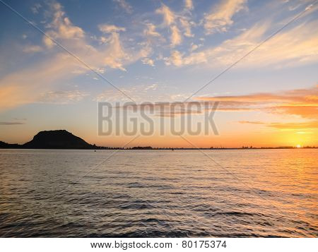 Mount Maunganui silhouetted on horizon as a golden sunrises.