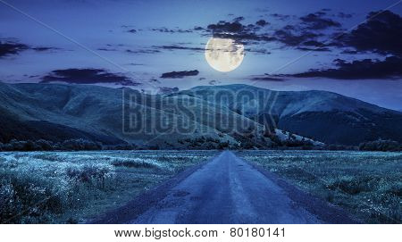 Abandoned Road Through Meadows In Mountain At Night