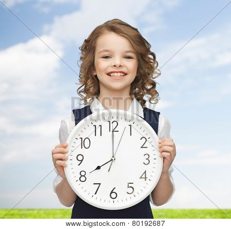 people, time management and children concept - smiling girl holding big clock showing 8 o'clock