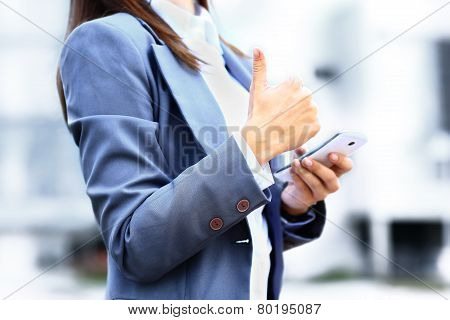 Pretty young business woman using mobile phone outdoor and ok sign