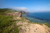 Fog moving to a rock from the sea. Primorye Russia poster