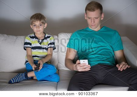 Child Watching Tv And Dad Using Phone