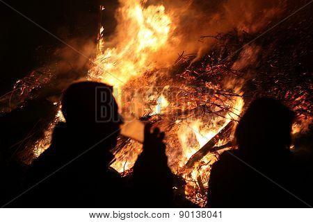 BURG, GERMANY - APRIL 7, 2012: People look at the traditional Easter bonfire in the Lusatian village of Burg in Spreewald Region, Lower Lusatia, Brandenburg, Germany.