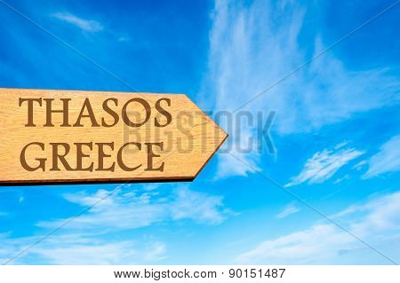 Wooden arrow sign pointing destination THASOS GREECE against clear blue sky with copy space available. Travel destination conceptual image poster