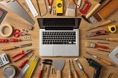 Laptop on a work table with DIY and construction tools all around top view hobby and crafts concept poster