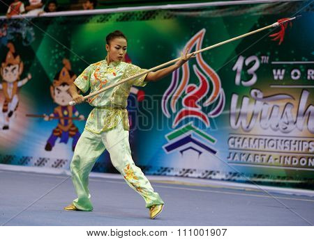 JAKARTA, INDONESIA - NOVEMBER 15, 2015: Sandi Oo of Myanmar performs the movements in the women's Qiangshu (spear) event at the 13th World Wushu Championship 2015 held in Istora Senayan, Jakarta.