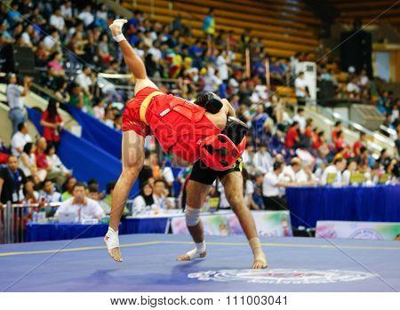 JAKARTA, INDONESIA - NOVEMBER 15, 2015: Jafar Topraghlou of Iran (black) fights Jorge Cortez of USA (red) in the men's 65kg Sanda event at the 13th World Wushu Championship 2015 in Istora Senayan.