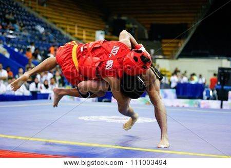 JAKARTA, INDONESIA - NOVEMBER 15, 2015: Puja Riyaya of Indonesia (red) fights Van Tai Nguyen of Vietnam (black) in the men's 70kg Sanda event at the 13th World Wushu Championship 2015 in Jakarta.