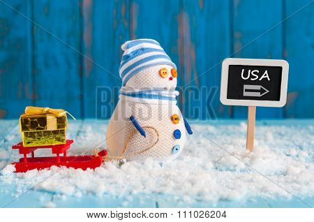 United States new year concept. Signpost with word USA and Snowman With gift, red sled stand near di