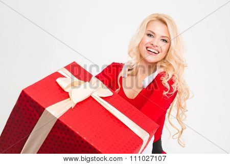 Cheerful joyful young female smiling and holding big red present box over white background