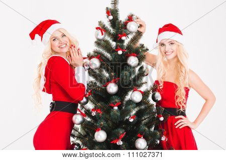Two smiling cute sisters twins in red santa claus dresses and hats standing near Christmas tree over white background