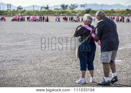 Man Helps Woman Put On Survivor Sash At Breast Cancer Walk