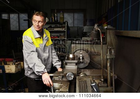 Old Turner Is Standing Near The Lathe.