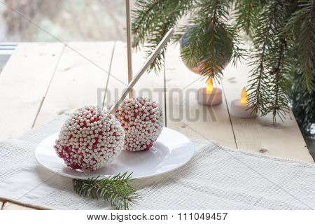 Apples in caramel with rice balls coating on Christmas and New Year background decor closeup