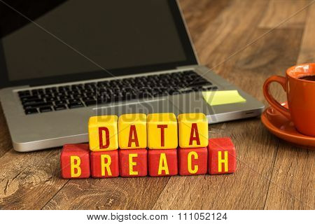 Data Breach written on a wooden cube in a office desk