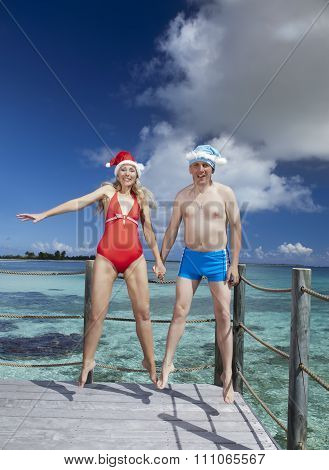The man and the woman in New Year's Santa-Klaus cap jumps on background of sea