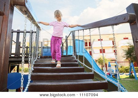 Little Girl Standing On Suspension Bridge On Playground, Hands On Rails