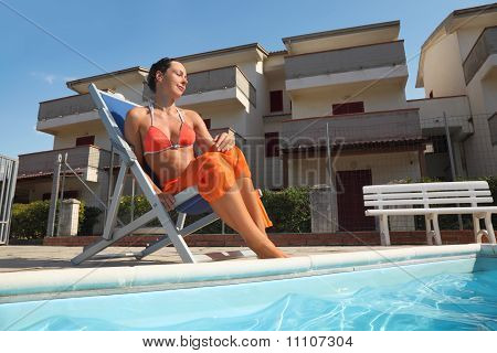 Young Woman In Orange Bikini And Pareo Sitting On Beach Chair Near Pool With Closed Eyes And Smiling