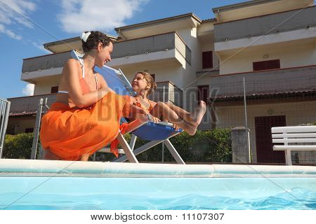 Young Mother In Orange Pareo And Daughter Sitting On Beach Chair Near Pool And Smiling