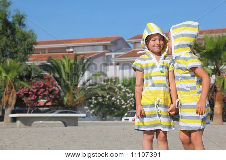 Two Little Girls Standing On Beach And Holding For Hands