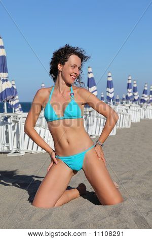 Beautiful Young Woman In Blue Swimsuit Kneeling On Beach. In Background Rows Of White Deck Chairs