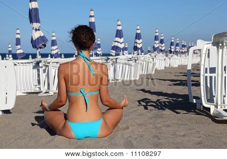 Beautiful Young Woman In Blue Swimsuit Seats On Beach. In Background Rows Of White Deck Chairs
